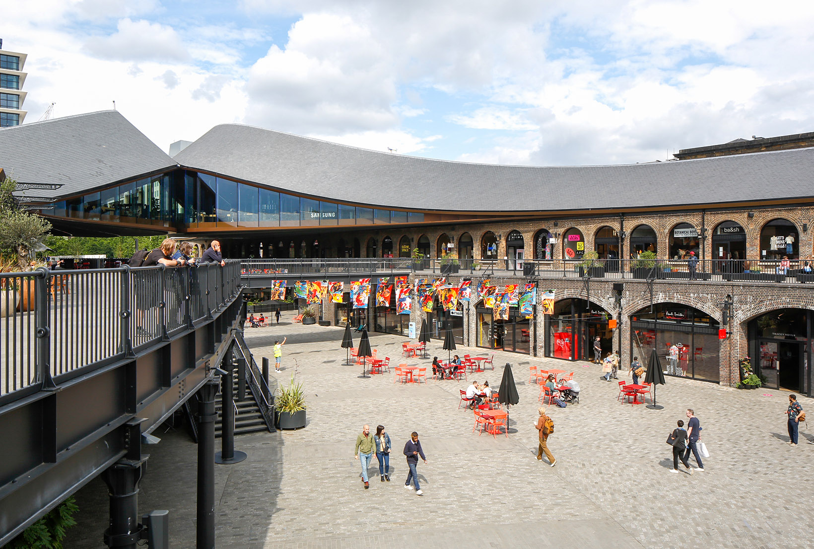 Zoomed out shot of Coal Drops Yard, with the multicoloured raised flags visible in the distance