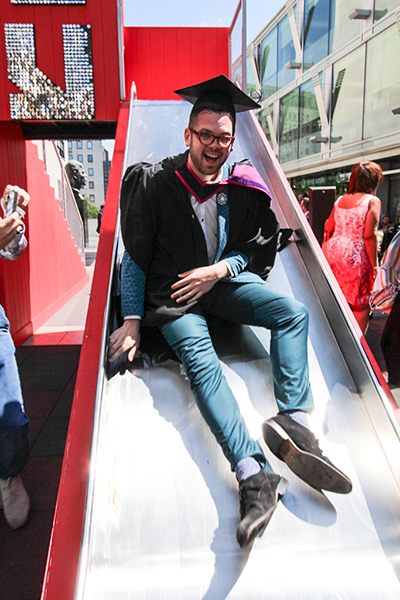 Liam Moore celebrates receiving his BA in Graphic Design Communication on one of the Southbank's slides.