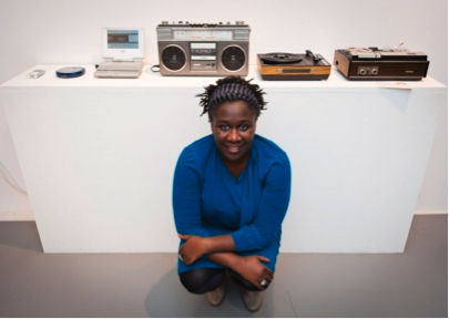 Photo showing artist and curator Barby Asante in front of exhibition display