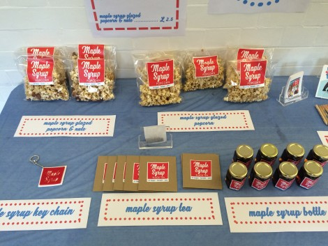 Eve Laguë's table selling her branded maple syrup goodies. Products include maple syrup covered popcorn, branded key chains, Maple Syrup Black Tea bags and small jars of Maple Syrup.