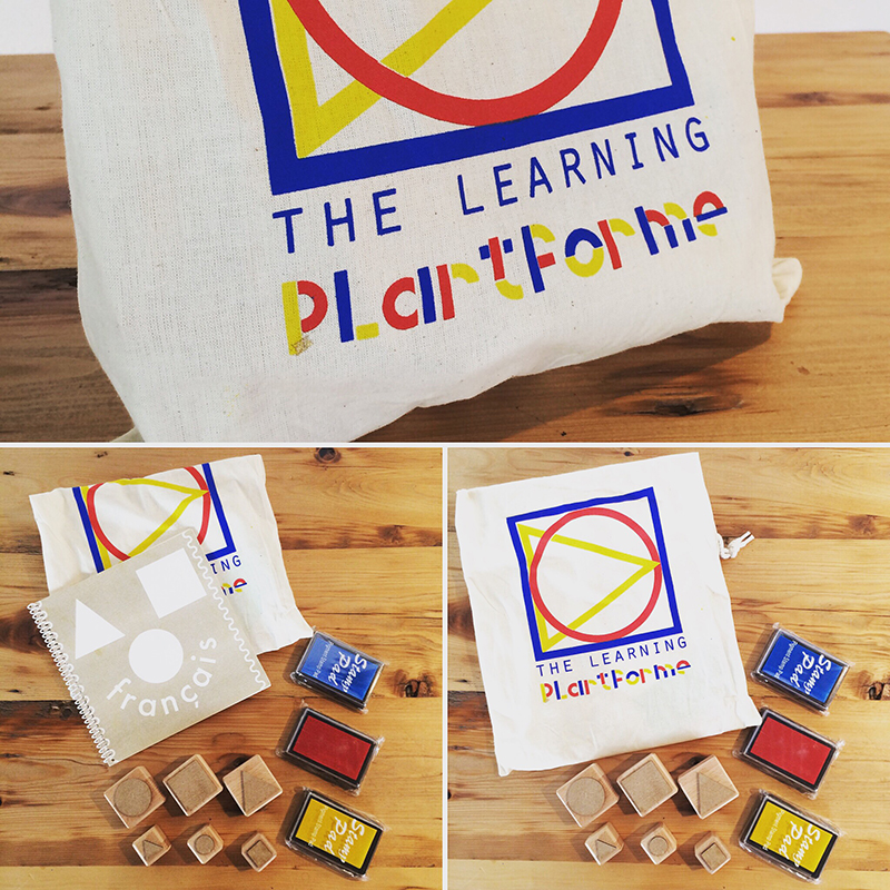 Eve Laguë, some playful objects she has made. Simplistic, allowing those who interact with them to explore playful avenues upon interaction. The objects are geometric stamps, ink pads, a note book, all stored in a blue, yellow and red decorated canvas bag.