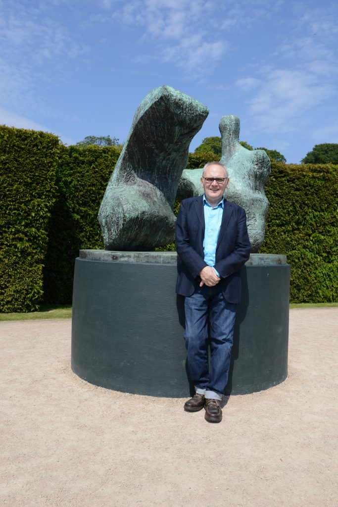 Peter Murray CBE with Chelsea's own Two Piece Reclining Figure No.1 1959, by Henry Moore, at Yorkshire Sculpture Park.