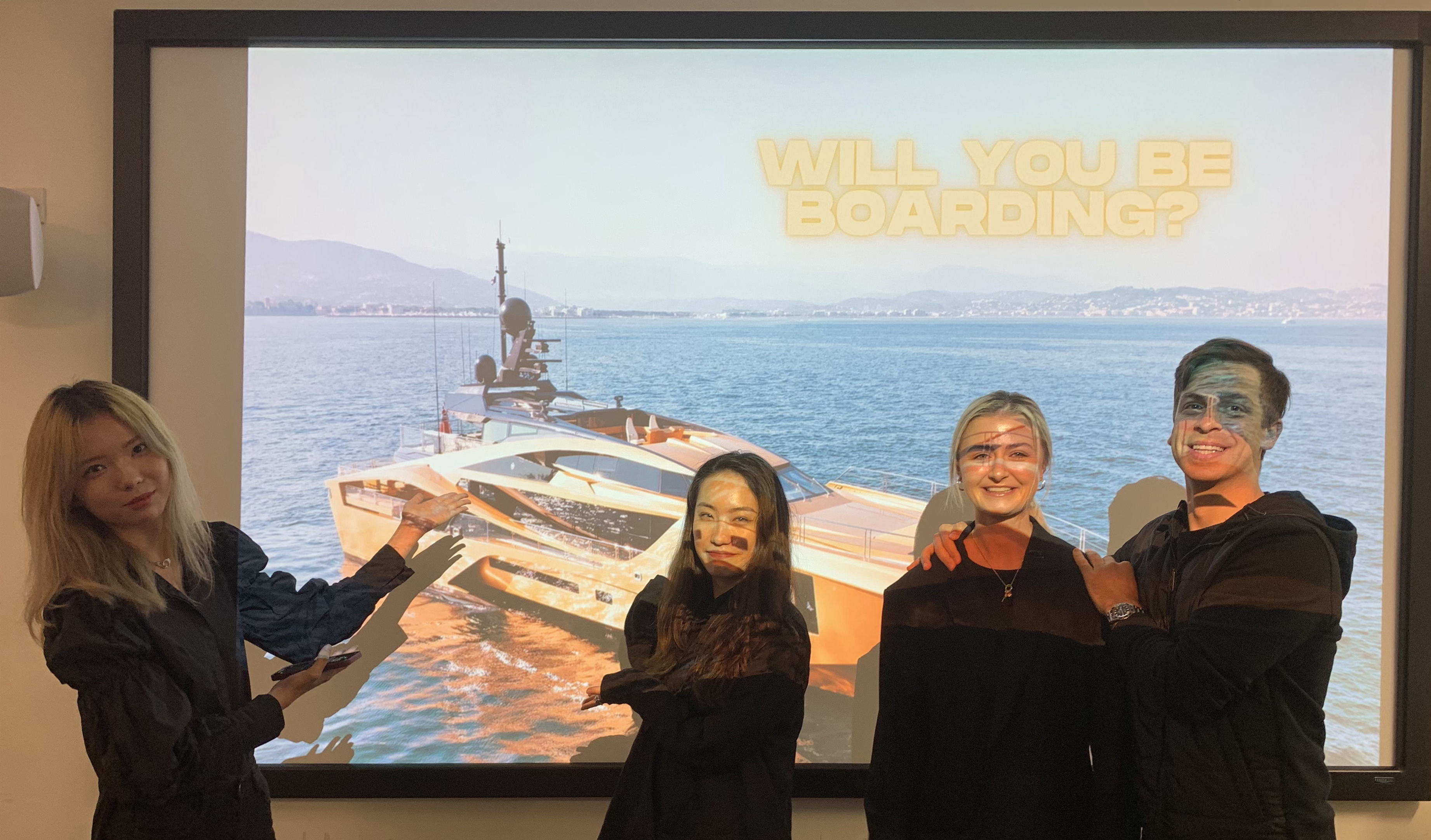 four students posed in front of a projector in a classroom