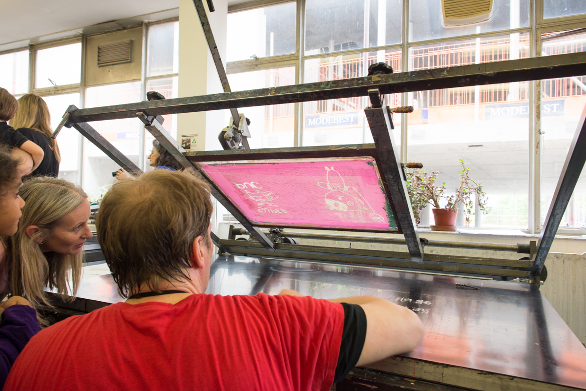 Print Technician Tony Lee checks a screen before printing onto a T Shirt