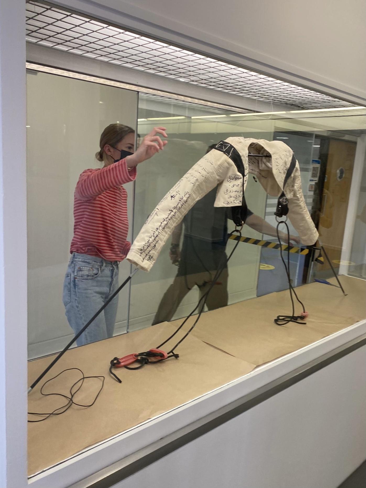 student installing display in vitrine