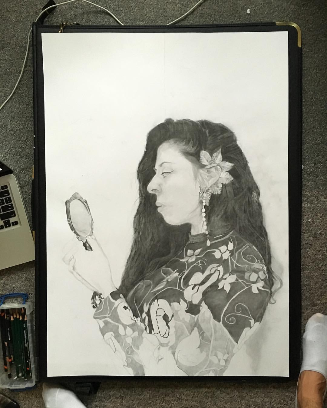 John Bingham's portrait in progress in black and white pencil of a woman with a floral jumper on, long wavy hair, a flower behind her ear and looking into a small elaborate mirror