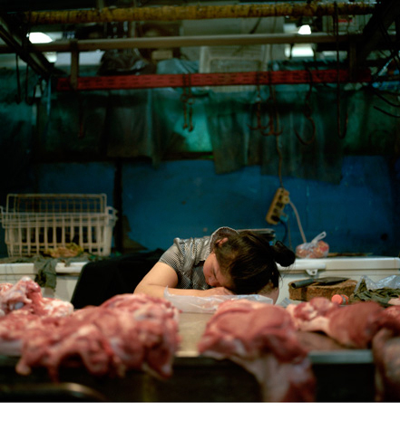 Photograph of person sleeping at a meat counter.
