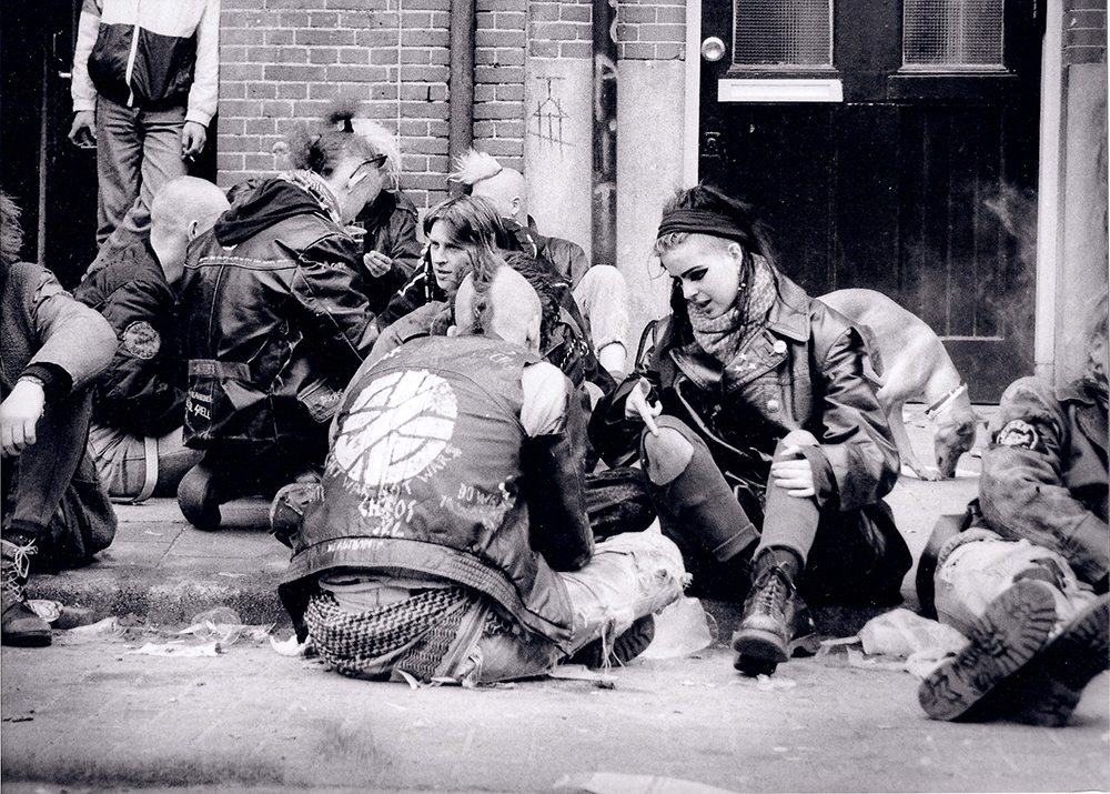 A black and white photo of a group of punks sitting outside on the ground in Amsterdam