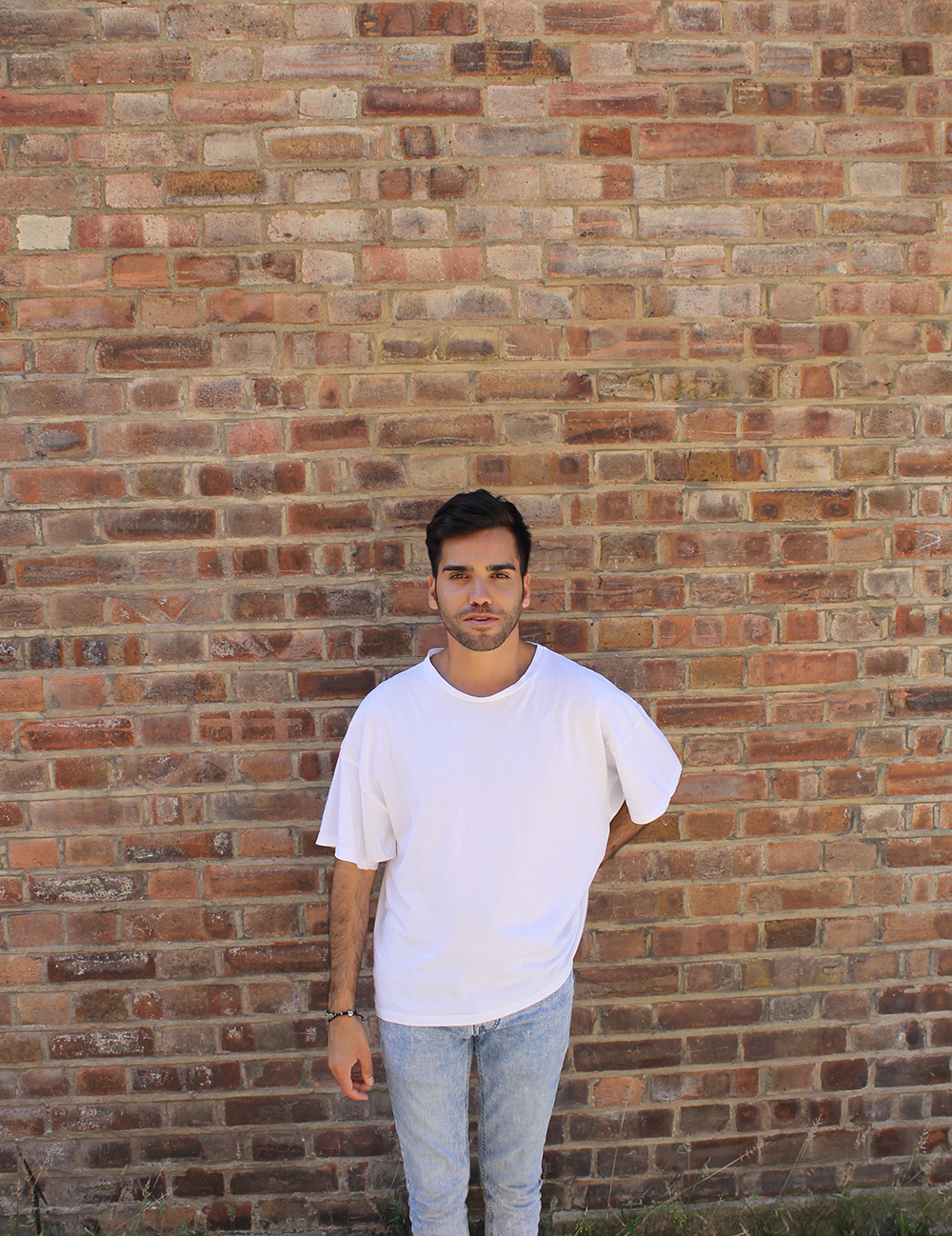 John Bingham in a white t-shirt and faded jeans standing in front of a red brick wall