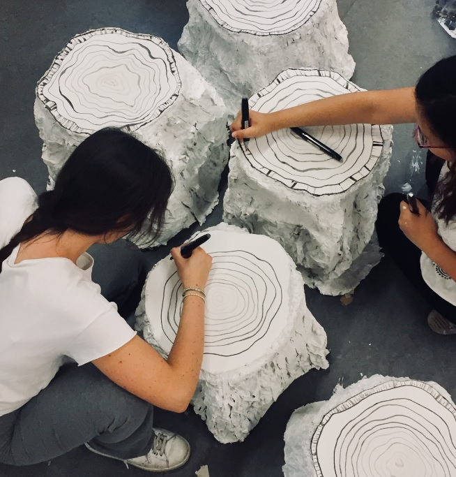 Students drawing rings on the tree stump stools that will be displayed around the campfire
