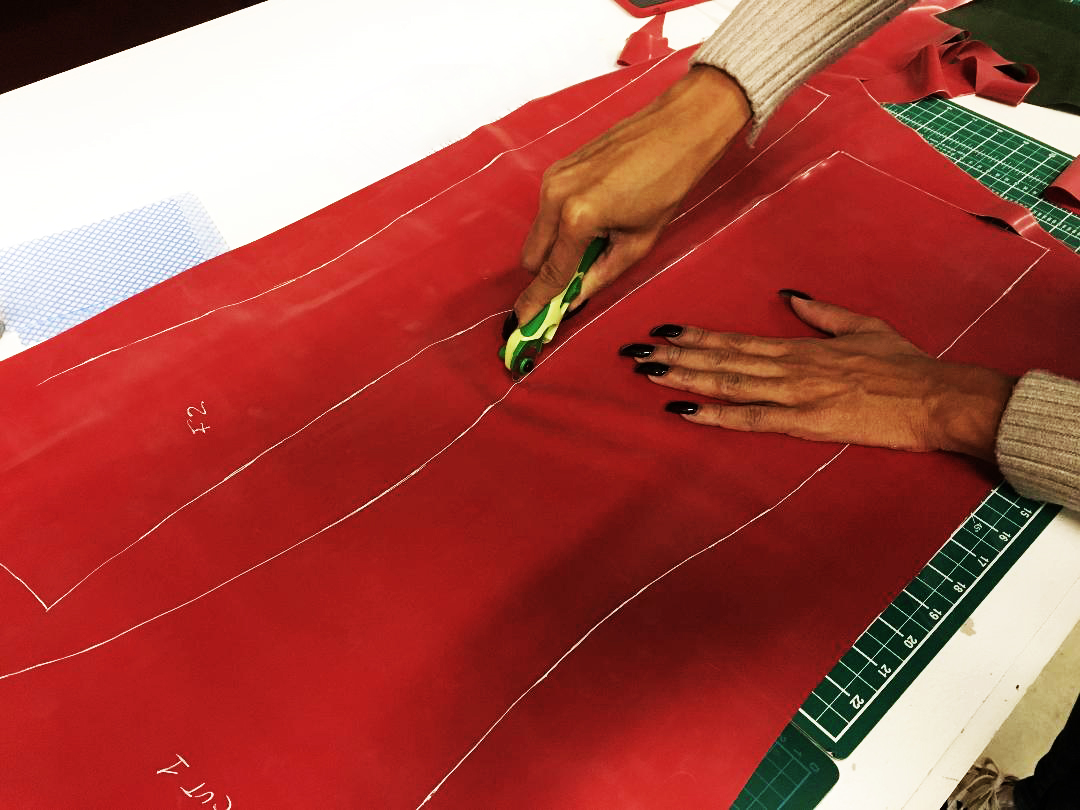 Image of red latex material being cut to the pattern