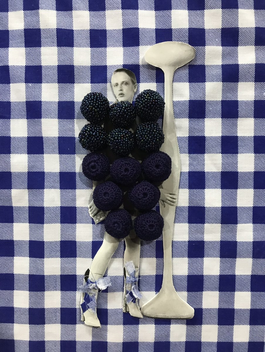 A magazine cut out of a model in black and white against a blue patterned fabric. The model's face is visible but their body is made up of blueberries as she leans against a pole.