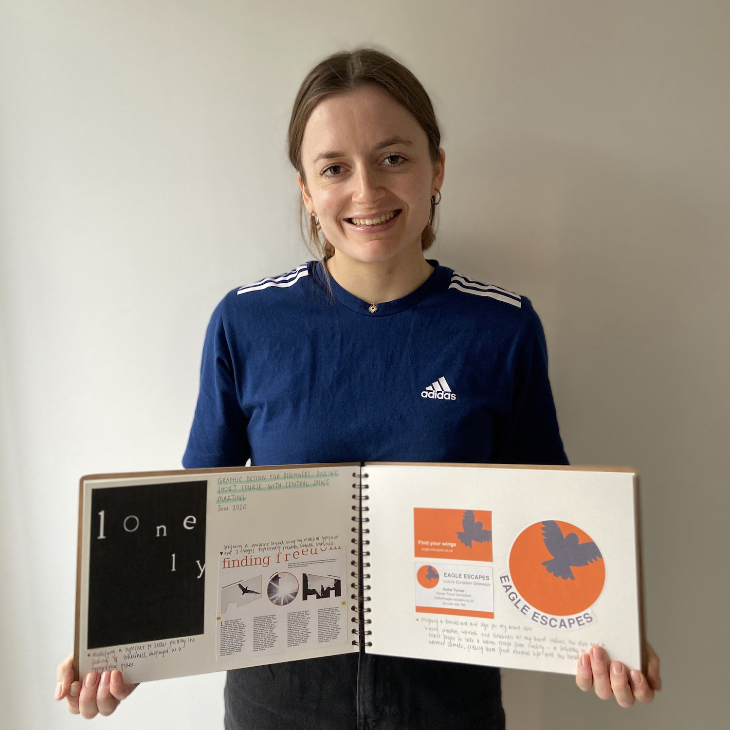 A photo of Sophie Turner holding her sketch book opened out and smiling to the camera