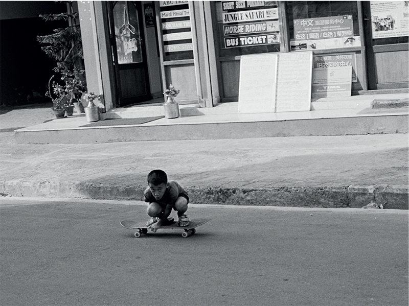 Photograph by Tom Caron-Delion, featured in a joint exhibition Thik Cha: An Exhibition for Nepal. The black and white photograph is of a young Nepalese boy crouching down on his skateboard on an empty road in front of a shop with many signs and potted plants.