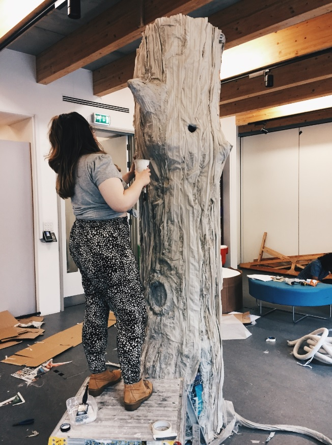Student working on a large tree prop for the set
