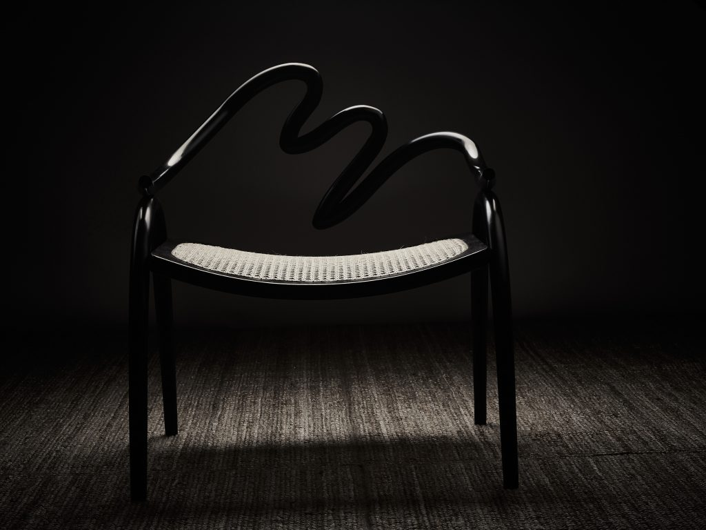 Armchair made from Ebonite, plywood and handwoven cane by Studio Swine