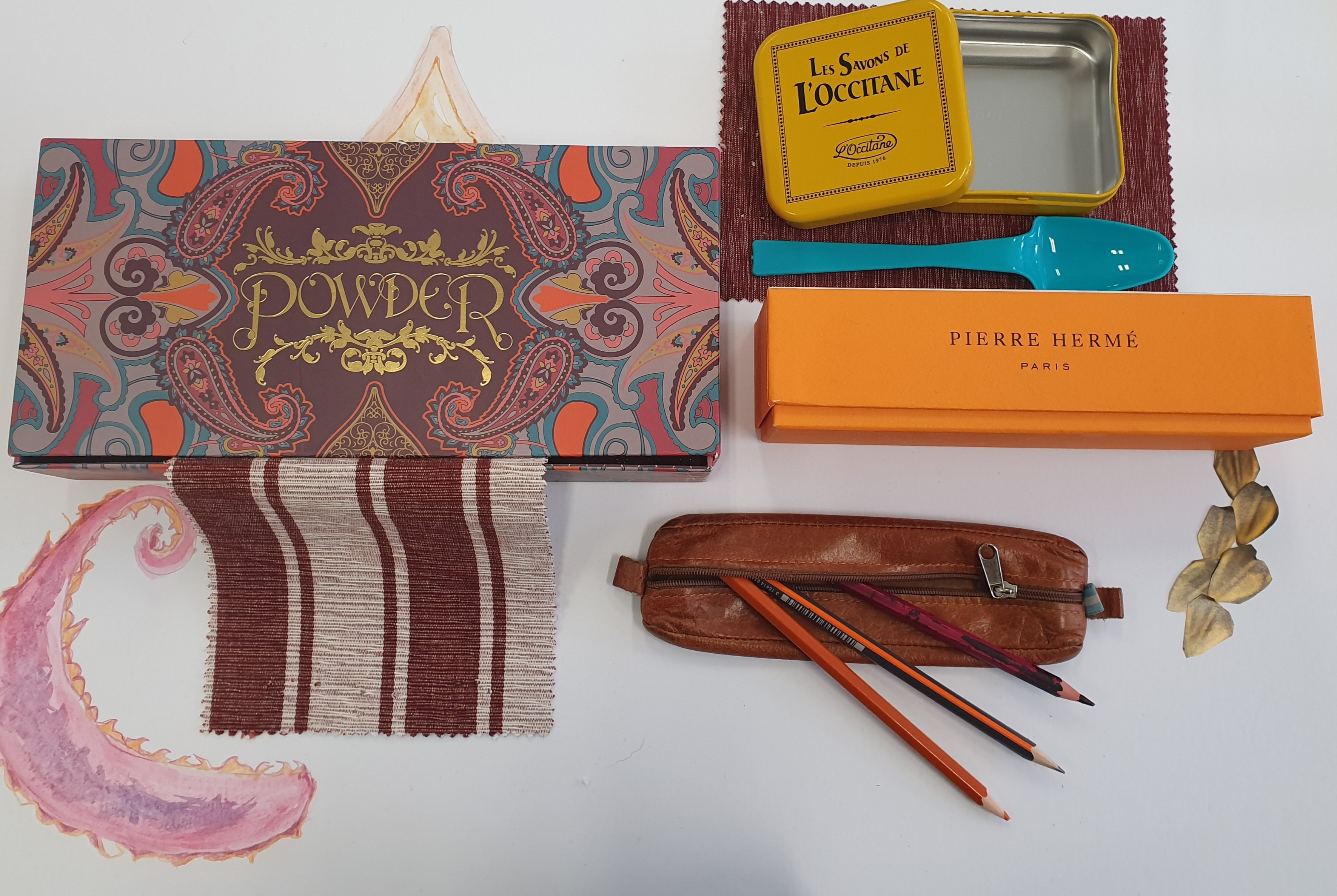 A mood board on a white background. A patterned case with the word 'Powder' is on the left of the board. To the right there is a small yello L'occitane tin open and a plastic blue spoon beneath it. There is also an orange rectangular box from Pierre Hereme and a brown leather pencil case with three pencils poking out of the pencil case diagonally.
