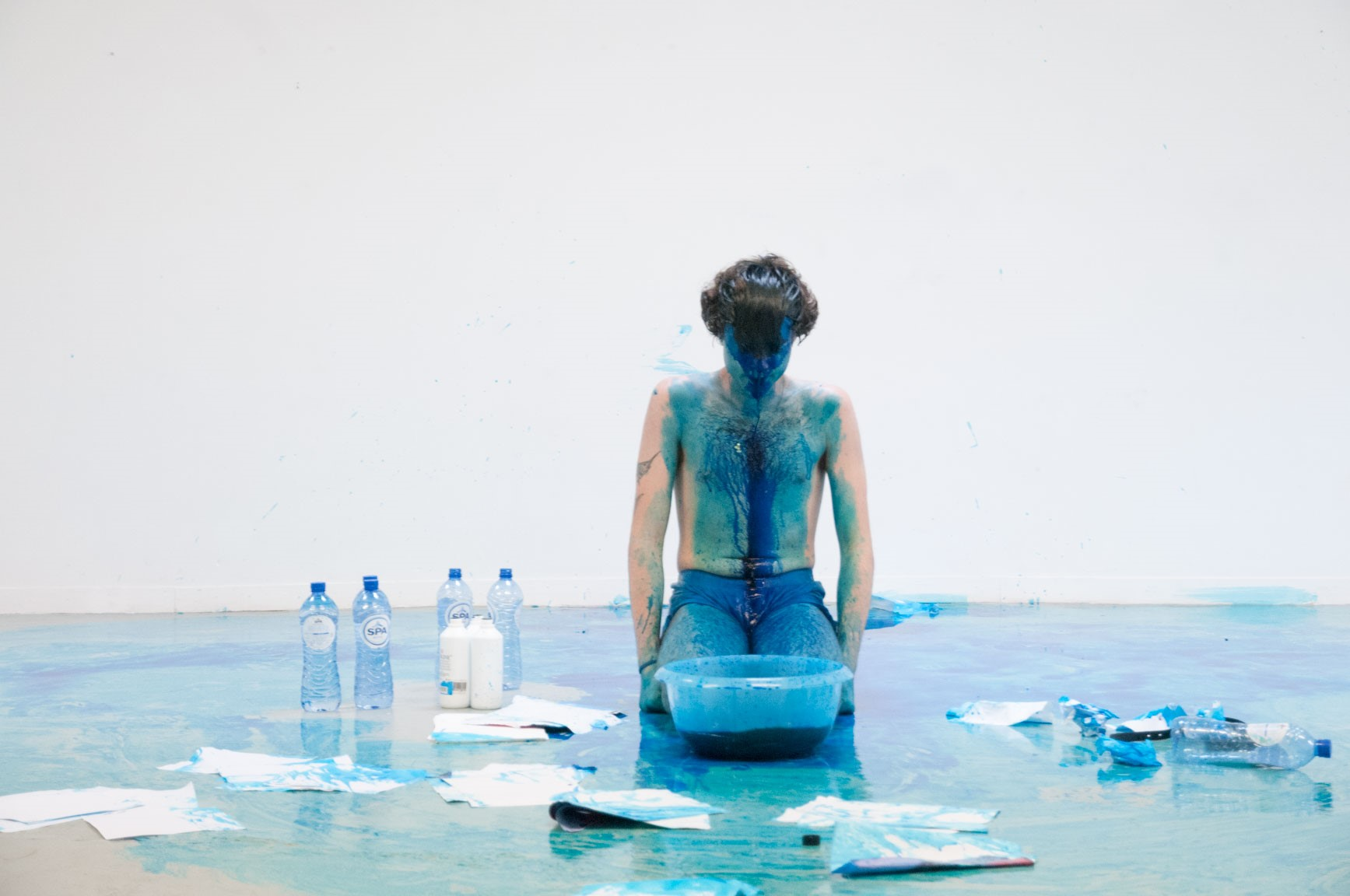 Giovanni kneels in a white room with a bowl of blue ink in front of him, he wears no shirt and is covered in blue ink diluted by water surrounded by paper, bottles of water and the blue ink.