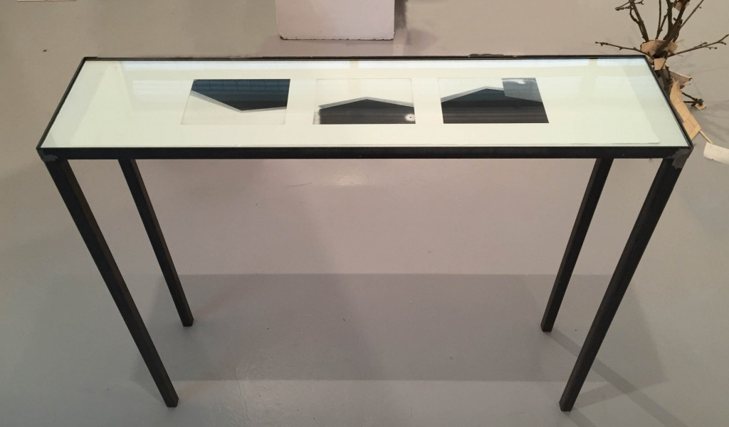 UNIT 2016: Harry Walker (BA Photography) - Tavolo. Black metal legged and rimmed glass top table containing 3 pohotgraphic prints of images of the gallery.