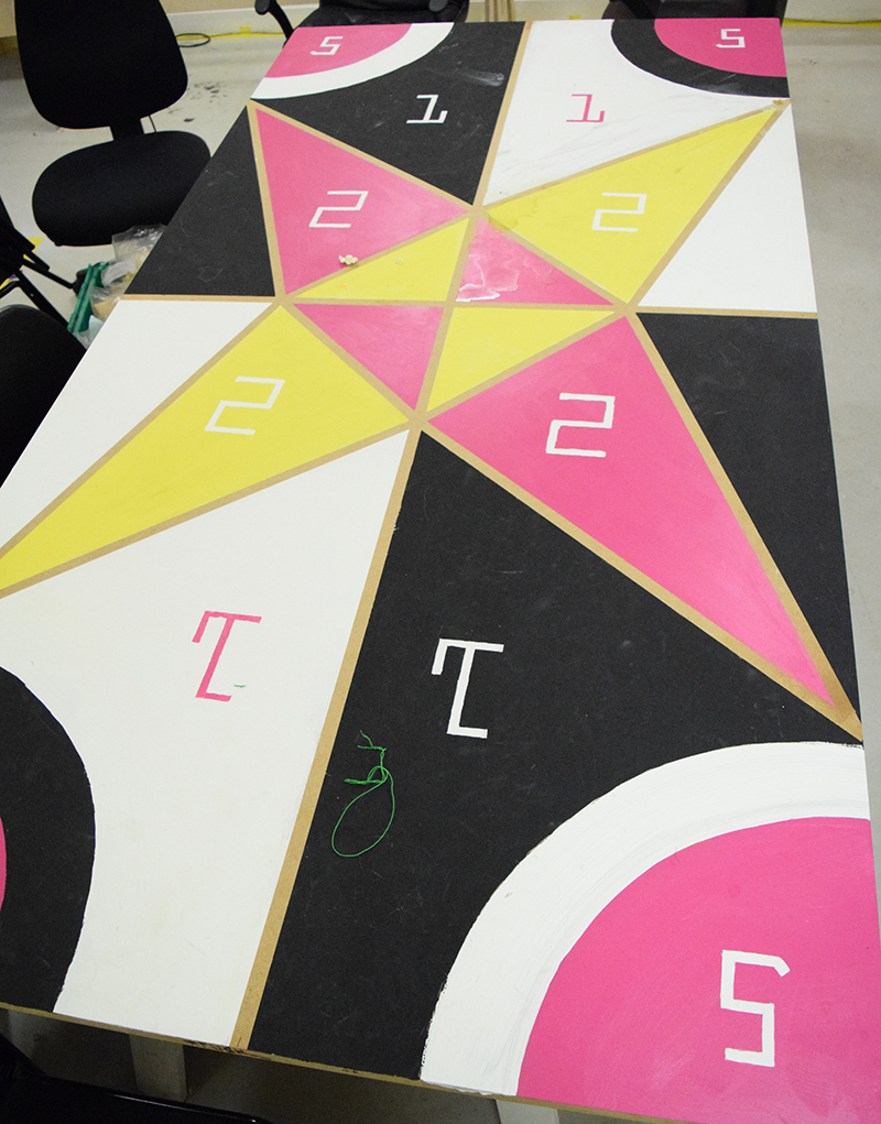 Patterned geometric table with a large star in yellow, pink black and white, painted with numbers for games
