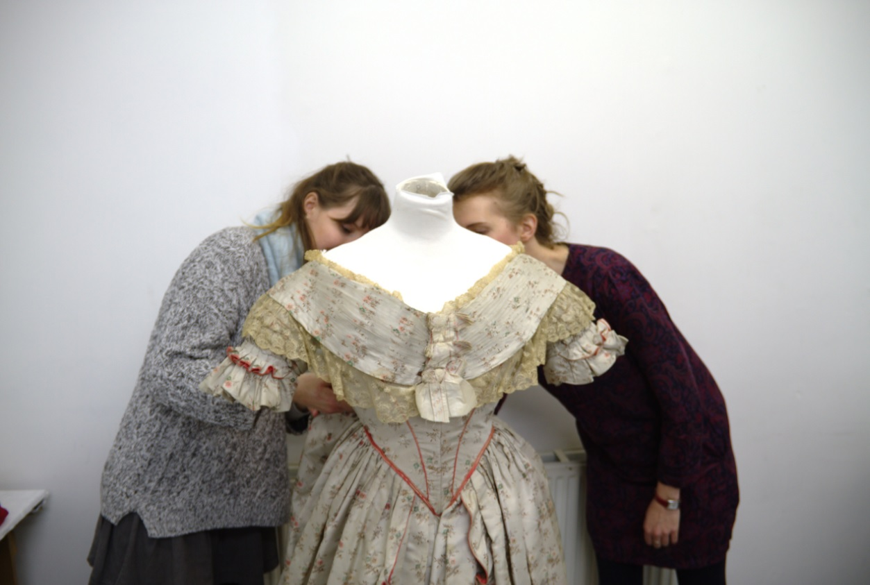 Volunteers working with one of John Bright's historical costumes