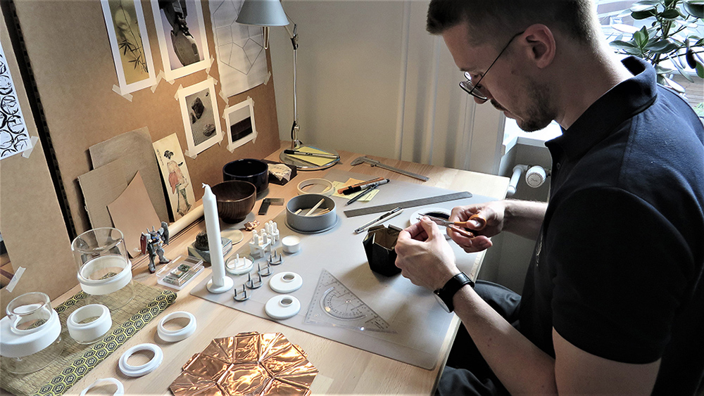 Alexander is at his desk working on a project. The desk is full of materials as he looks down to cut a piece with a pair of scissors.