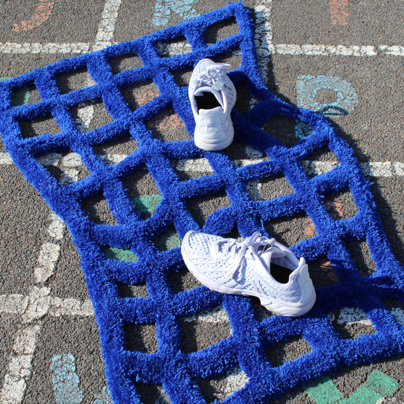 A pair of white shoes on a blue grid rug