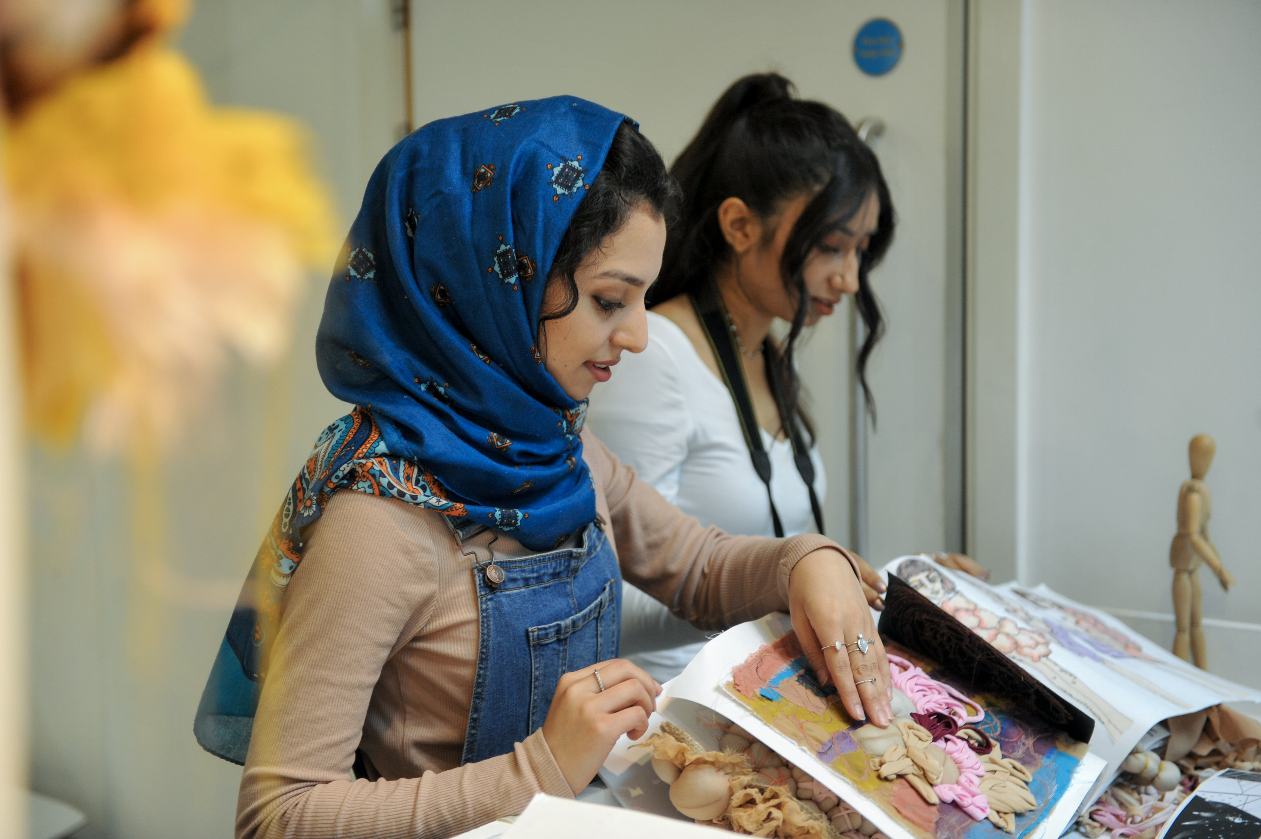 Two students looking through sketchbooks and samples of work