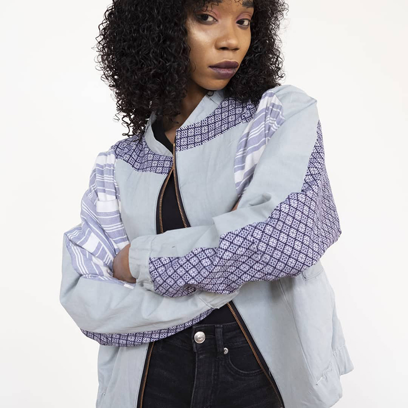 Woman wearing bomber jacket in grey and purple tones