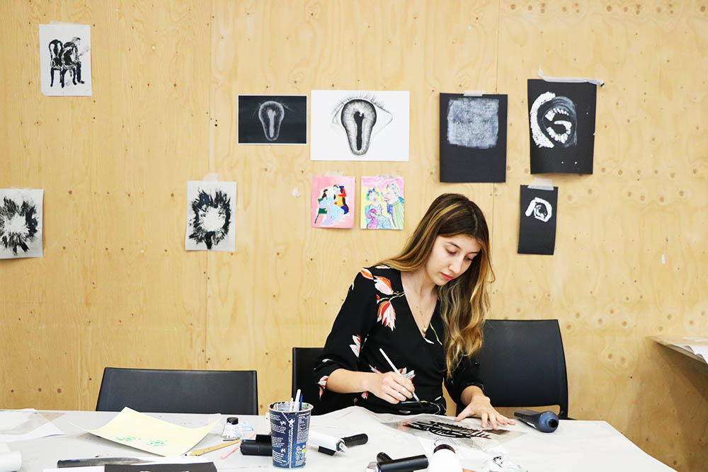 Valentina Schuchner working in a classroom with her illustration work pinned to a wall behind.
