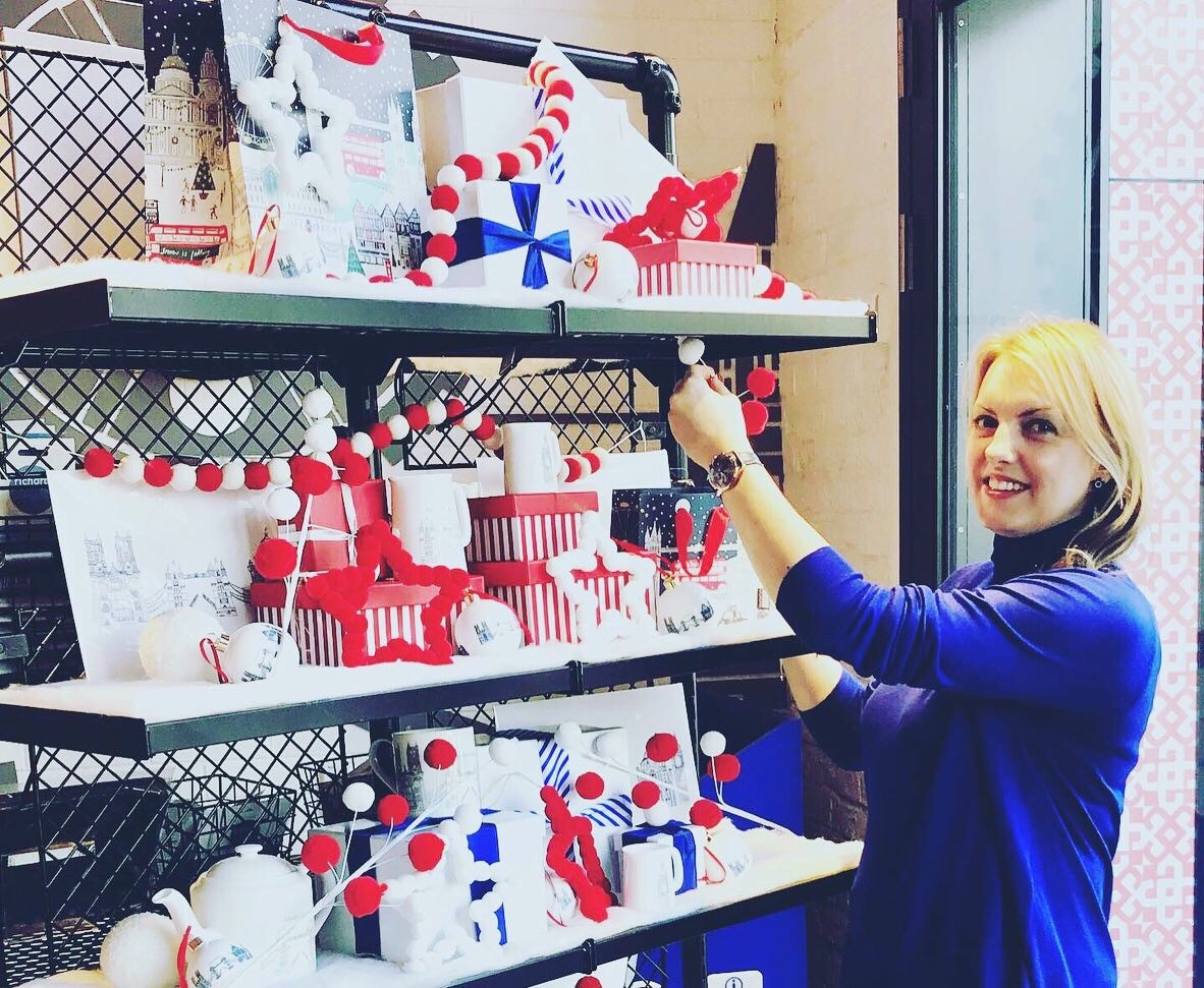 A Photo of Sarah Manning wearing a blue top standing alongside a Christmas display.
