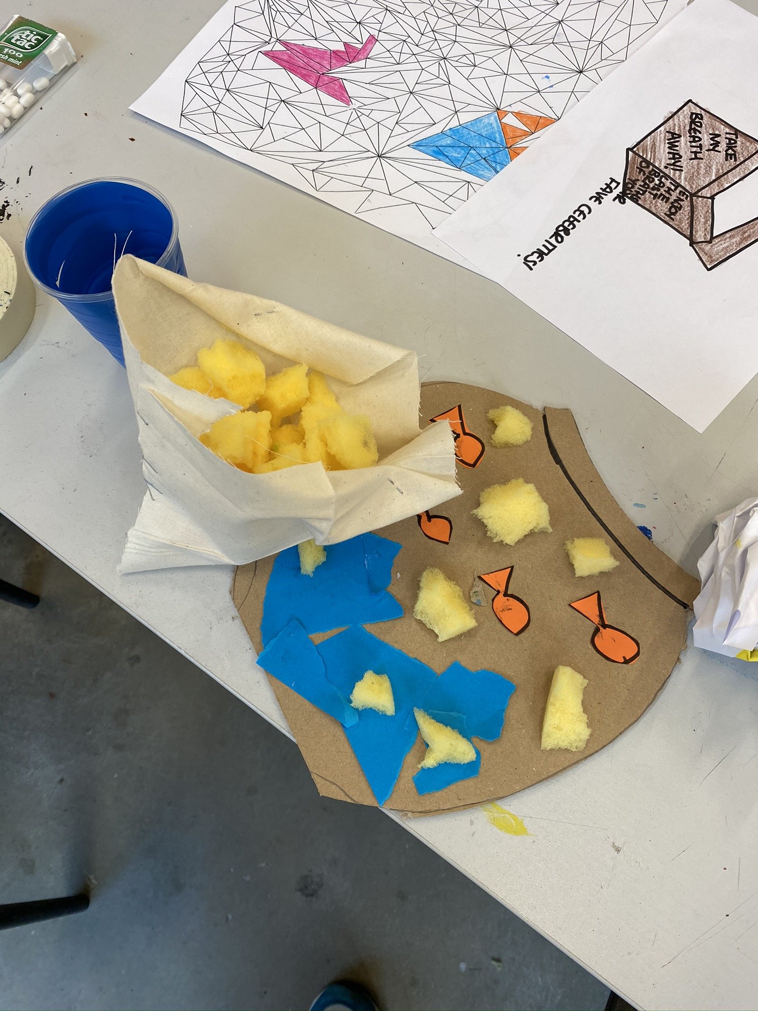 Cardboard and sponge on a table in the fashion of a fish bowl and a cone of chips