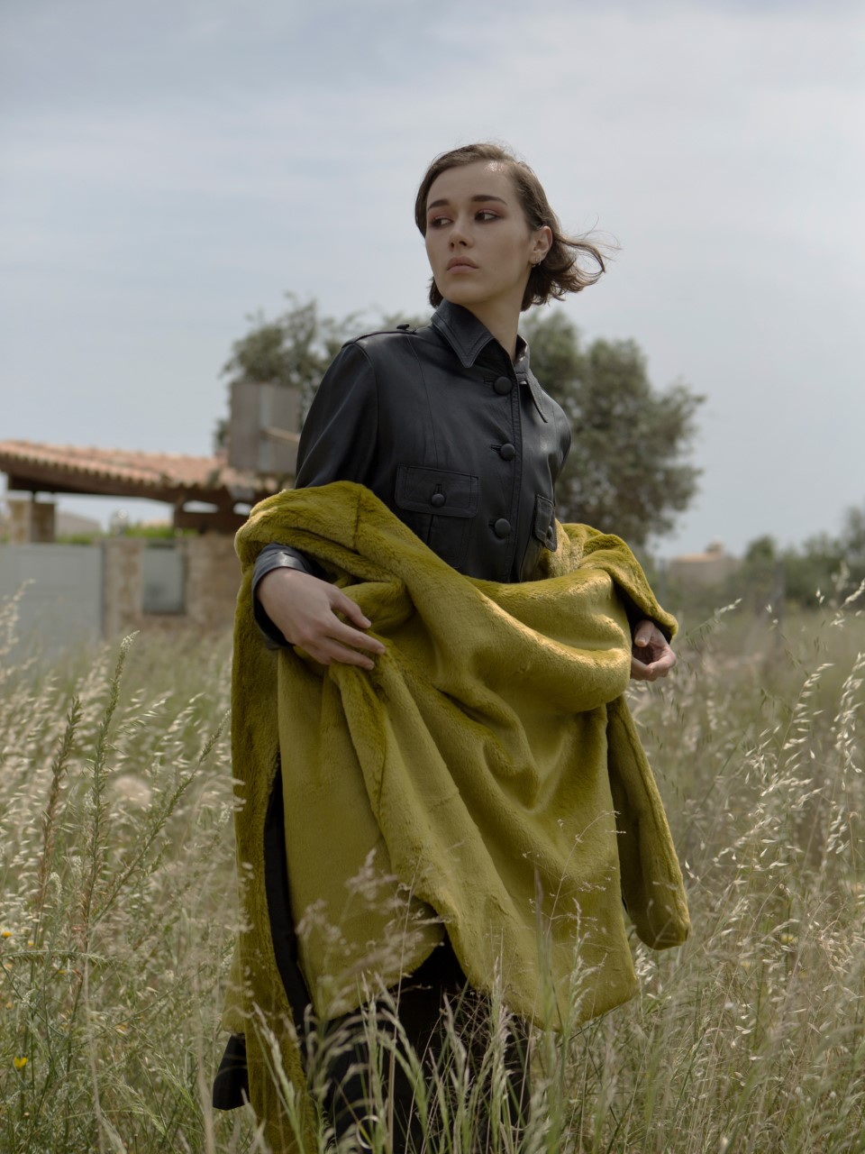 A model standing in a field wearing a baggy garment staring away from the camera