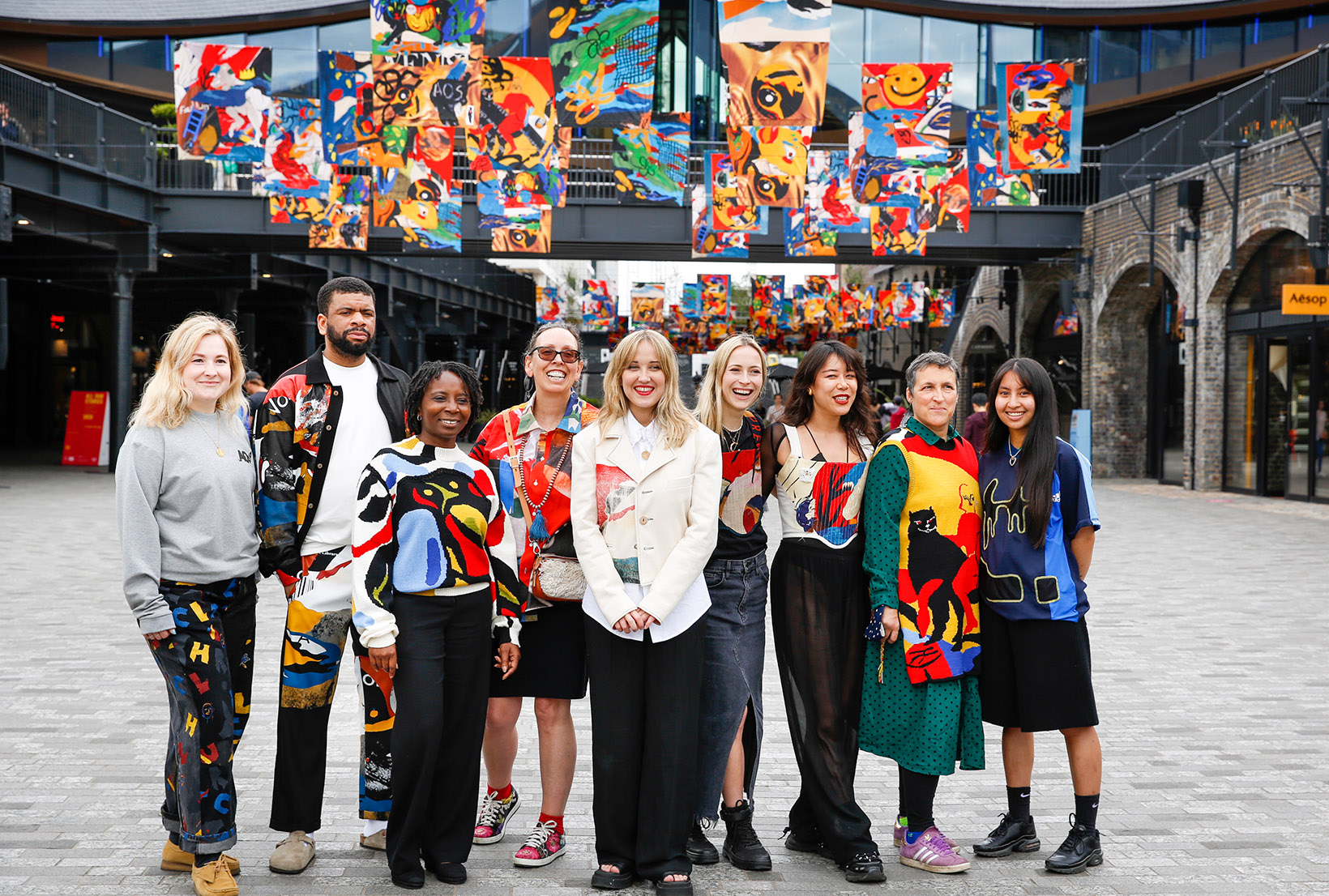 Image of Bethany Williams with members of The Magpie Trust, backed by the multicoloured flags.