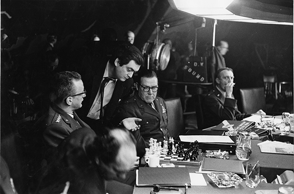 Stanley Kubrick on set with cast in the war room.  Image from the Stanley Kubrick Archive held at the University of the Arts London supplied with thanks to the SK Film Archives LLC, Sony Colombia, the Kubrick family, and University of the Arts London