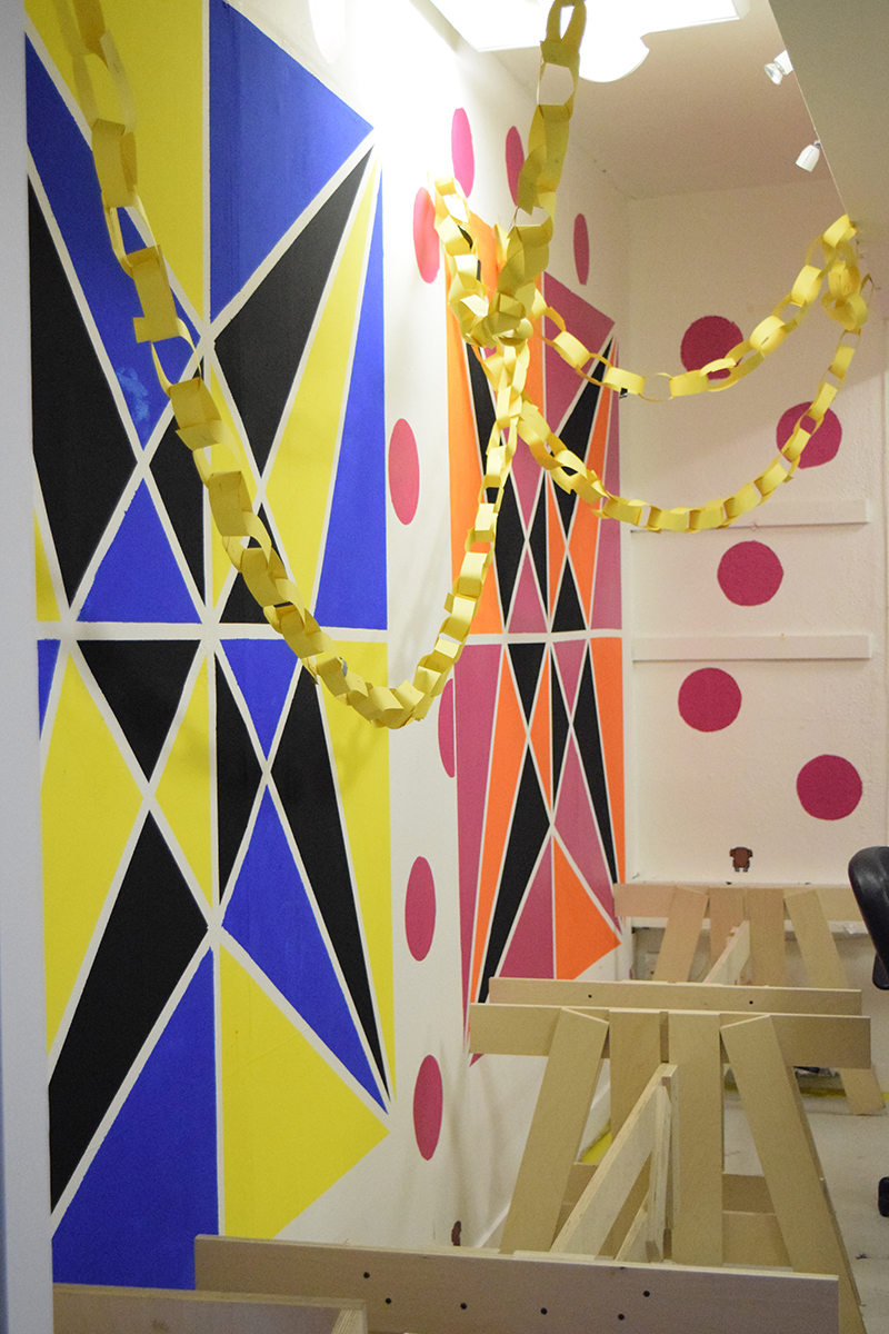 Geometric wall designs-stars in squares, one is blue, yellow and black, the other pink, yellow and black, at the 2015 Post Modern Christmas Party