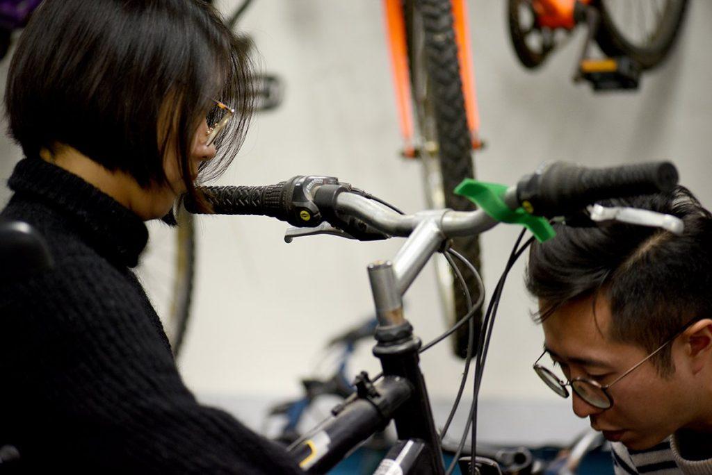 LCC graduates helping to fix bikes at the Bike Project