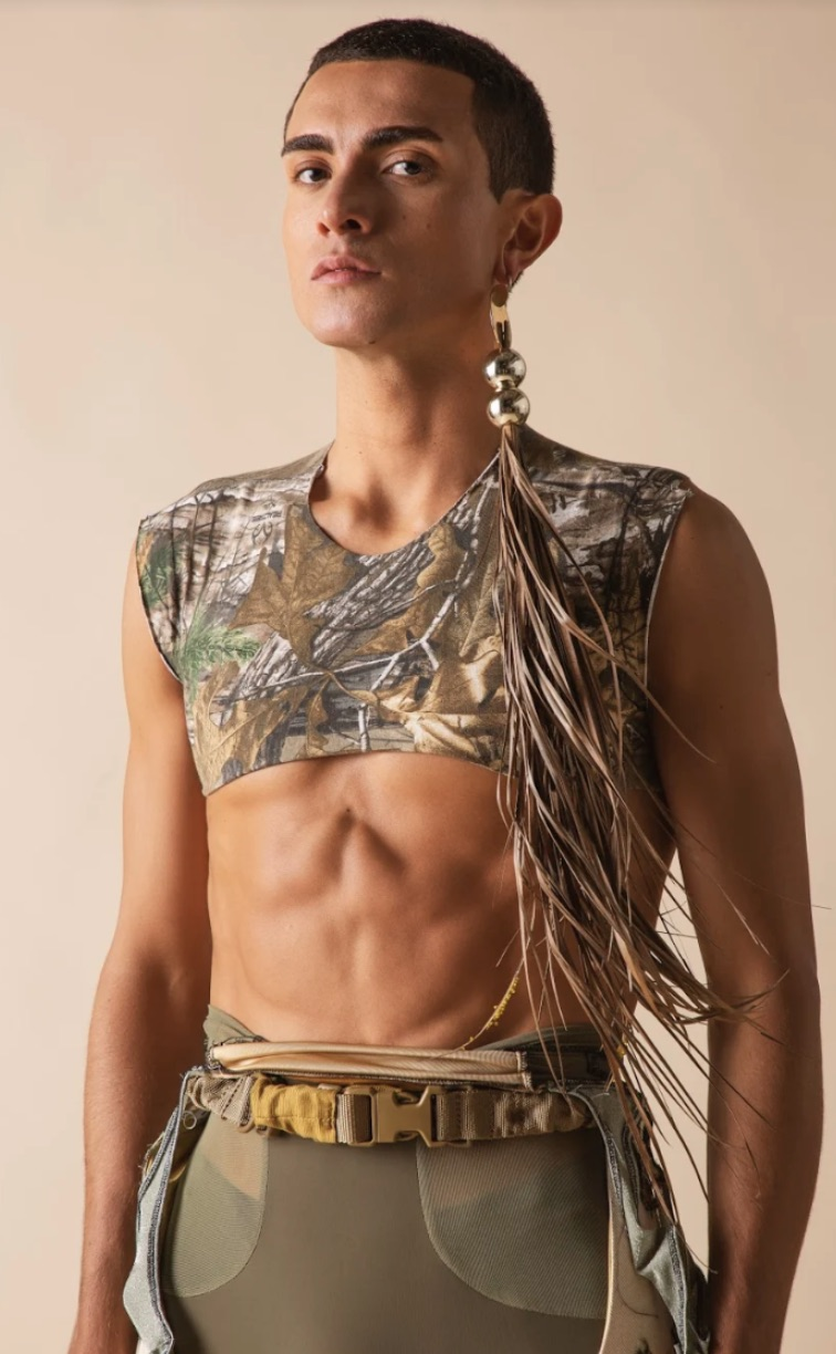 A photo of a model with a long dangling earring on their right ear with tassels. The model is wearing camouflage colours and the top they are wearing is cropped baring their stomach.