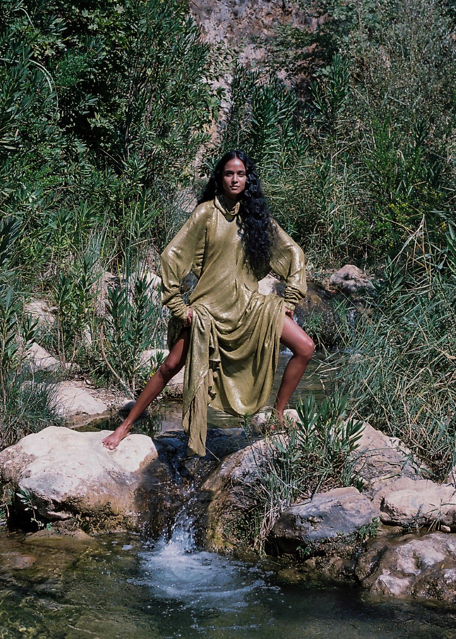 A woman wearing an olive dress standing wide legged on two boulders in the river