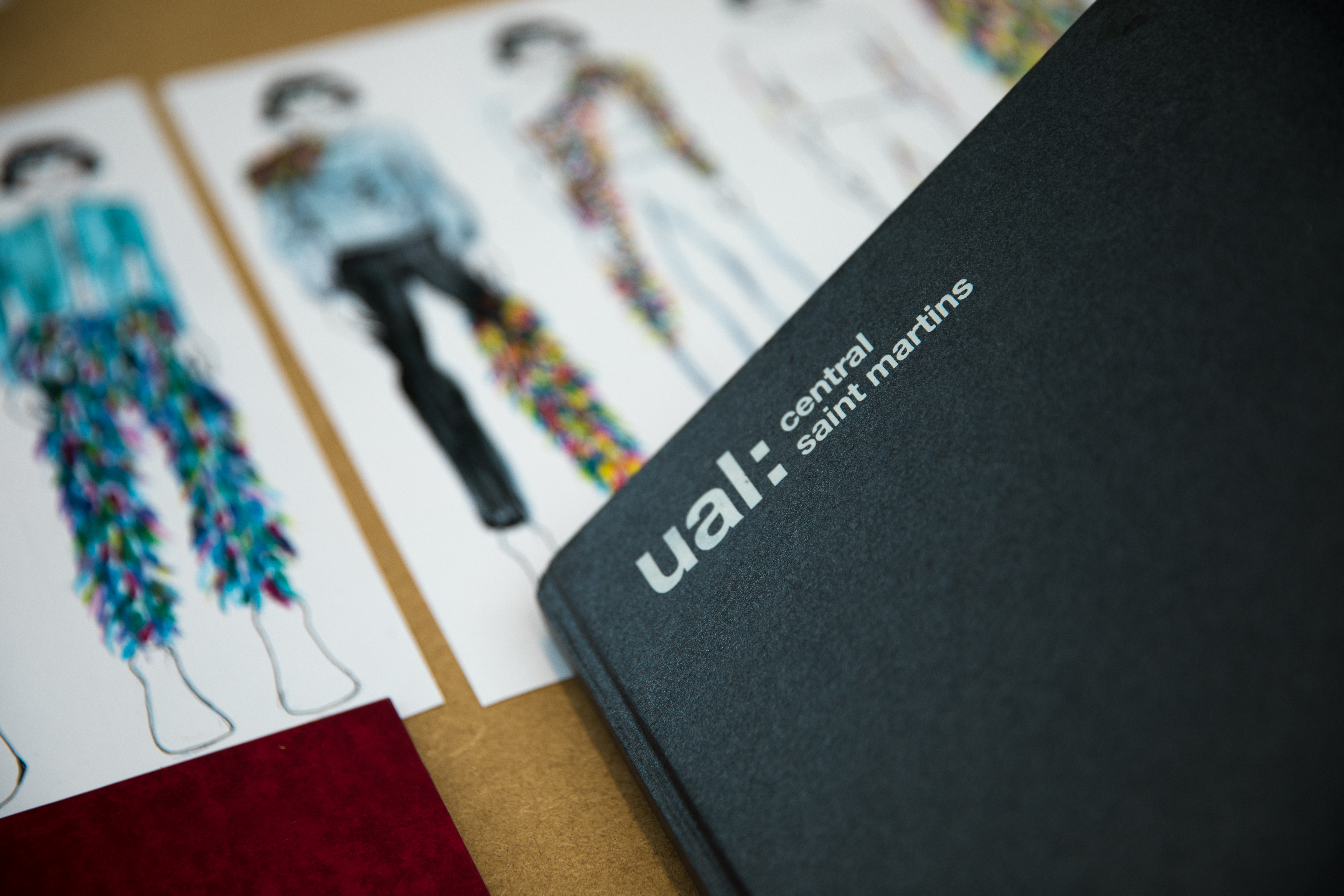 Black notebook with UAL Central Saint Martins Logo. Students work in background