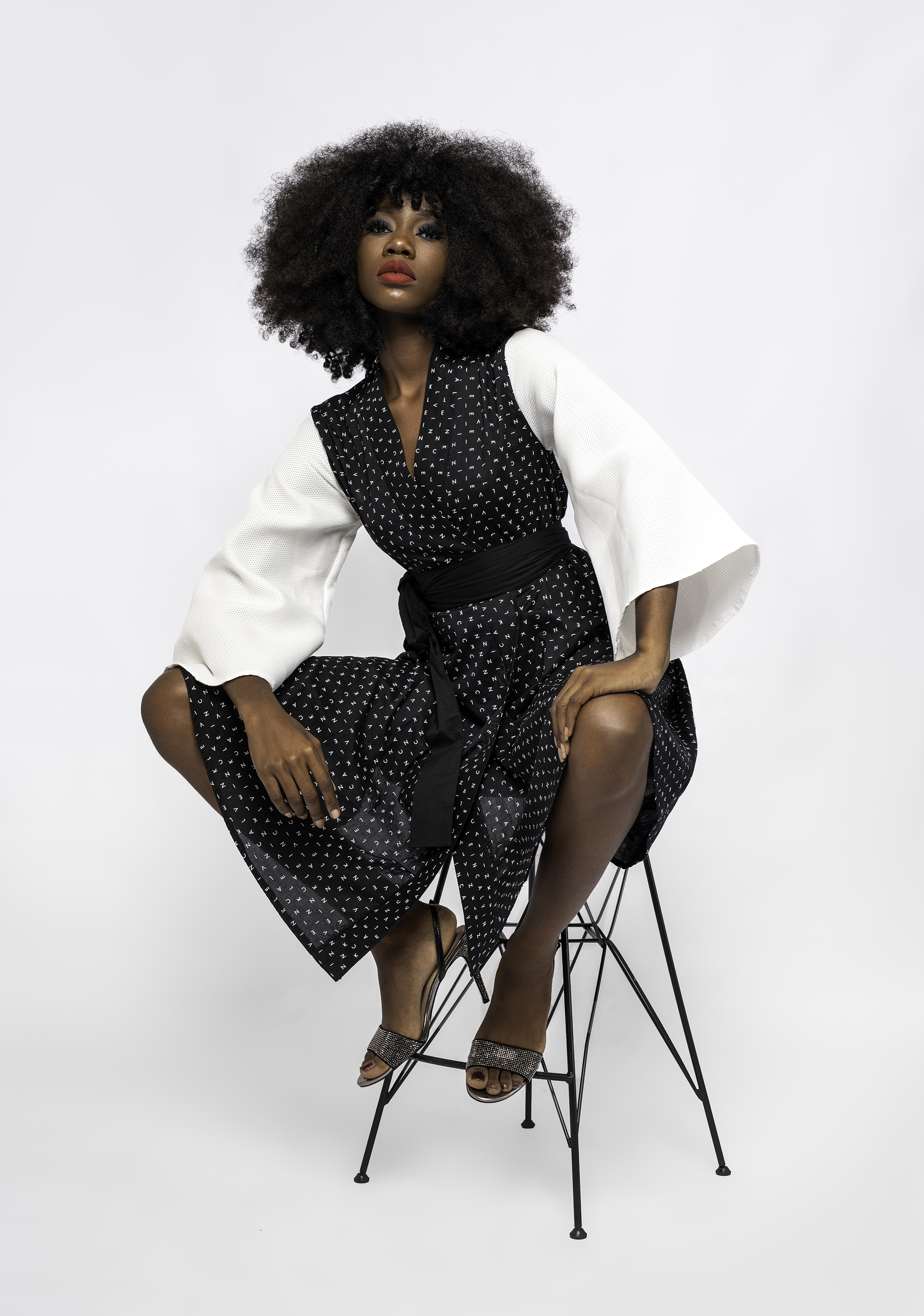 Model sitting on chair wearing Bolupe's designs.