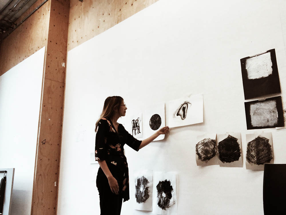 Valentina Schuchner in a classroom pinning her illustration work to a wall.