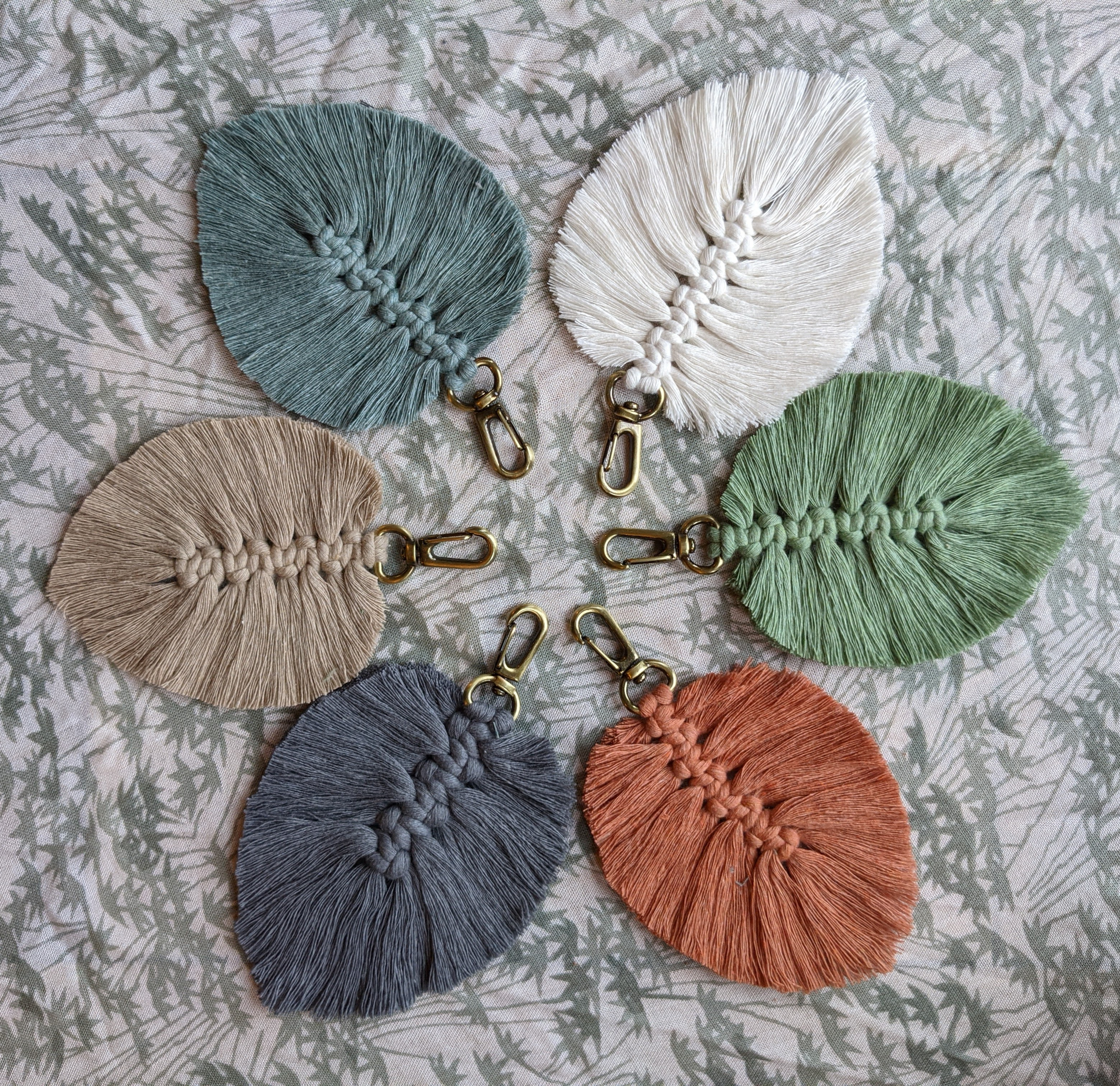 A collection of fabric key-chains positioned in a circle. Each key chain is in the shape of a leaf.