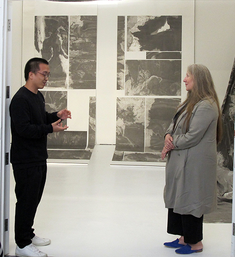 A man discusses his work with Anita Taylor. Artwork in background