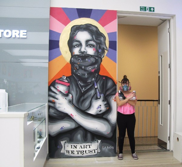 "'IN ART WE TRUST' is a spray painted piece by street art talent Zabou who stands next to her work in this image. The piece in Saatchi Store is of a young person with a bandanna covering their mouth, at the bottom is a banner saying ""IN ART WE TRUST"". The young person's arms are crossed over their chest, in one hand is a spray paint can, in the other is a paintbrush. The image is mostly grey, black and white except for blobs of paint scattered across the image. The young person has a yellow circle behind their head which looks like a halo, lines of orange, purple, blue and pink radiate out from this yellow circle."