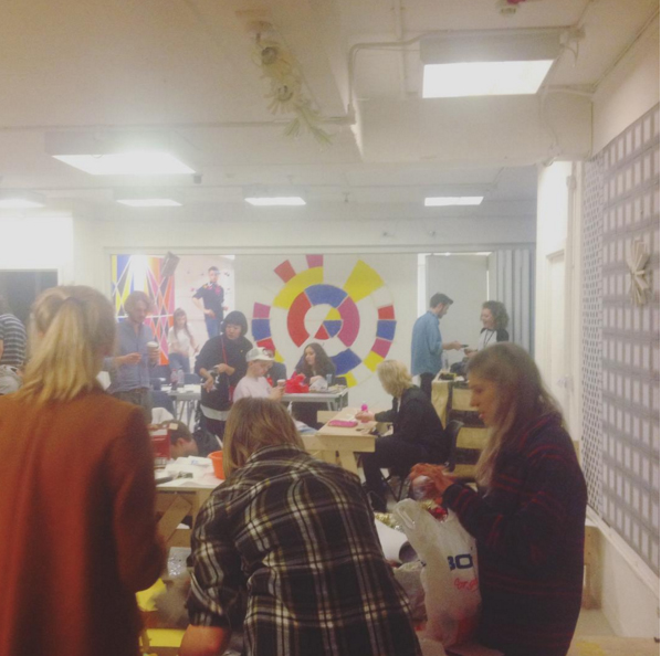 BA Graphic Design Students gather in the studio preparing for their Post Modern Christmas Party with a patterned wall backdrop and yellow paperchain garlands