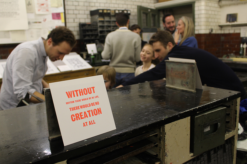 Photograph of exhibition in the letterpress workshop at Camberwell, typographic work in the foreground and staff and visitors can be seen taking part in a workshop in the background