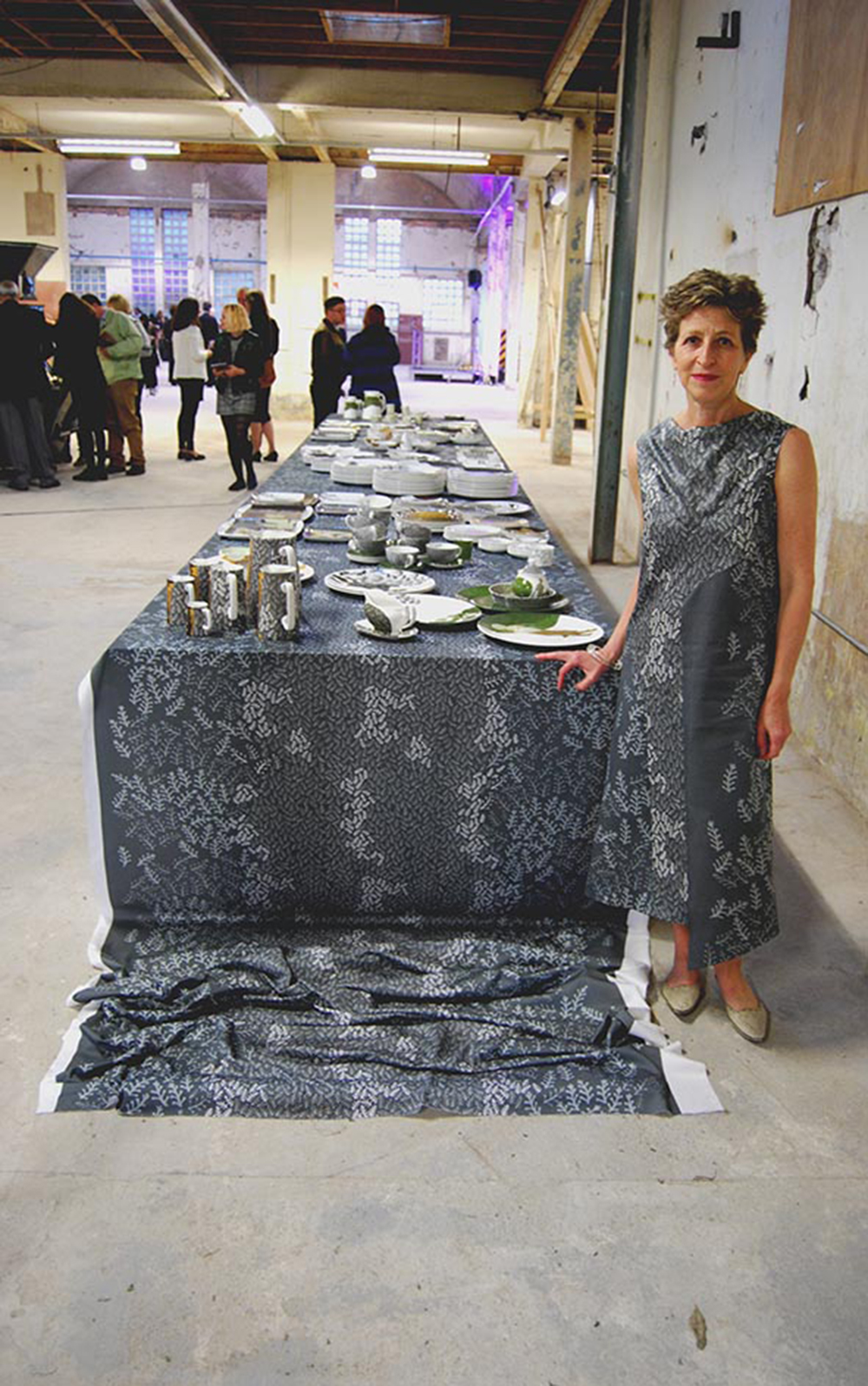 Charlotte Hodes next to the installation wearing a specially commissioned dress made by Wai Han, HO, an LCF MA Costume Design for Performance student