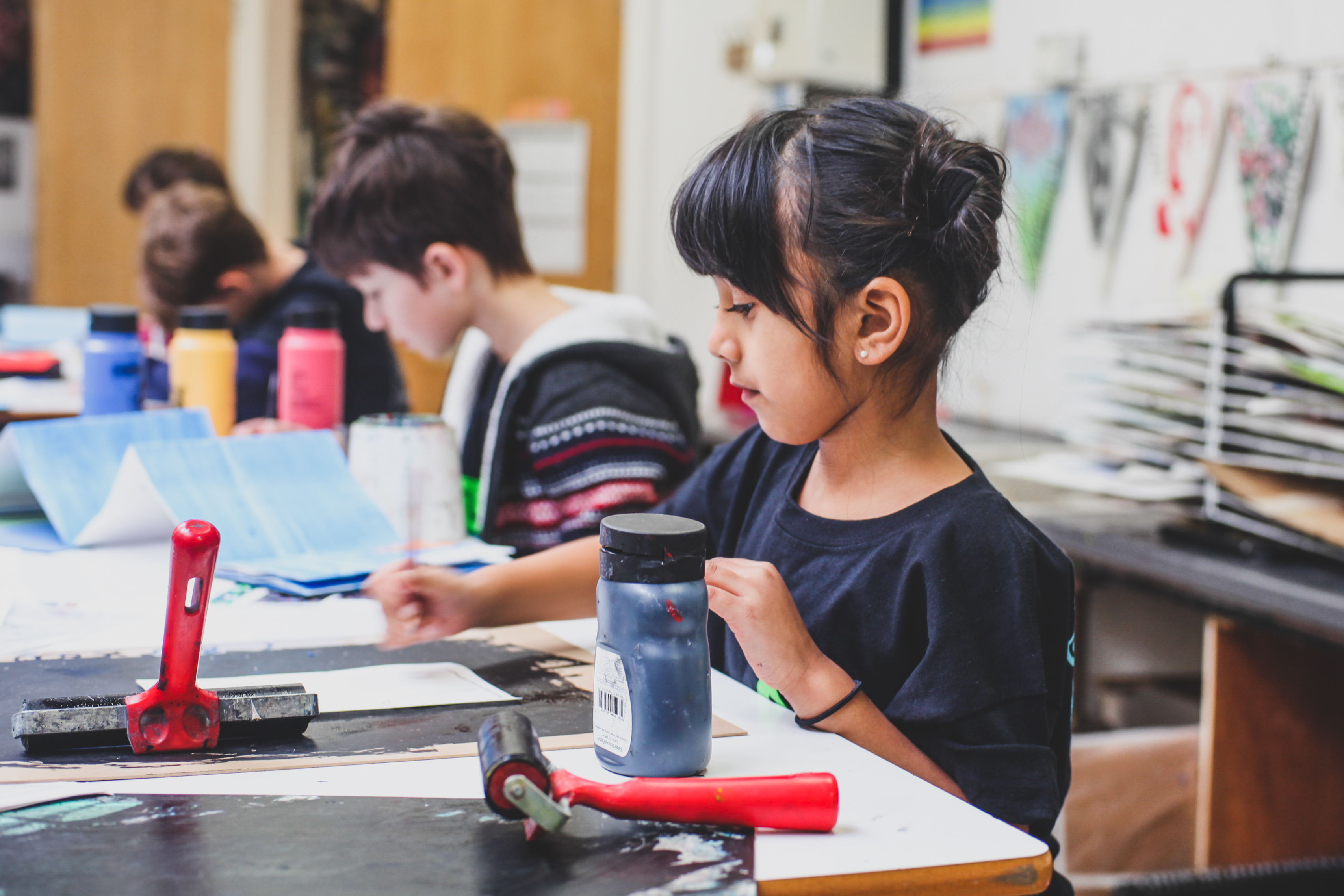 Young girl painting in class.