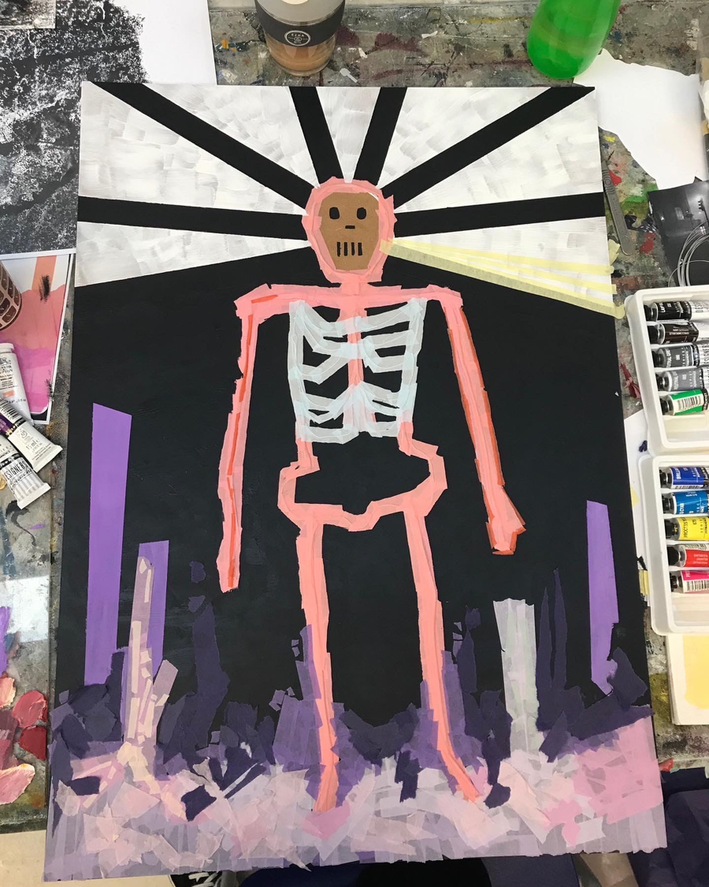 An image of the outline of a skeleton using oil paint. The skeleton stencil has been done with pink oil paint against a black board with purple streaks and lines at the bottom